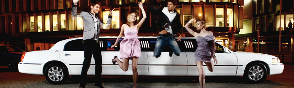 four Californians jumping for joy at night in front of a white color stretch limousine by 4 SEASONS limo service