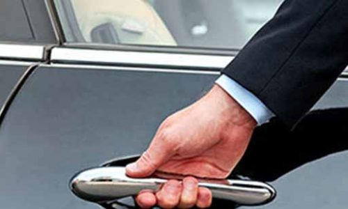 chauffeur opening Limousine door for corporate client